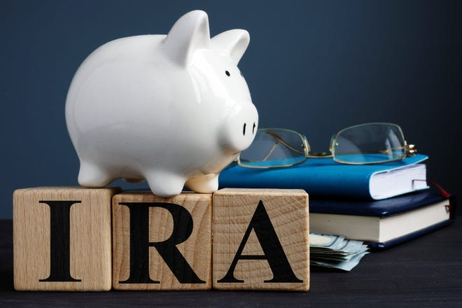 A piggy bank sitting on top of blocks with the letters I R A.
