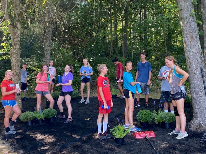 With the hands-on work completed by Owen Valley Middle School Athletic Director Justin Lowry and OVMS cross country coach Corbin Wrightsman, the OVHS course entrance recently received some much needed improvements. Generous donations of flowers and mulch from Harriman Farms and Greenhouse and Owen County Mulch allowed for the beautification of the entrance. The OVMS cross country team is shown as they water the flowers while Coach Wrightsman and AD Lowry are pictured with their shovels. (Submitted / Spencer Evening World)