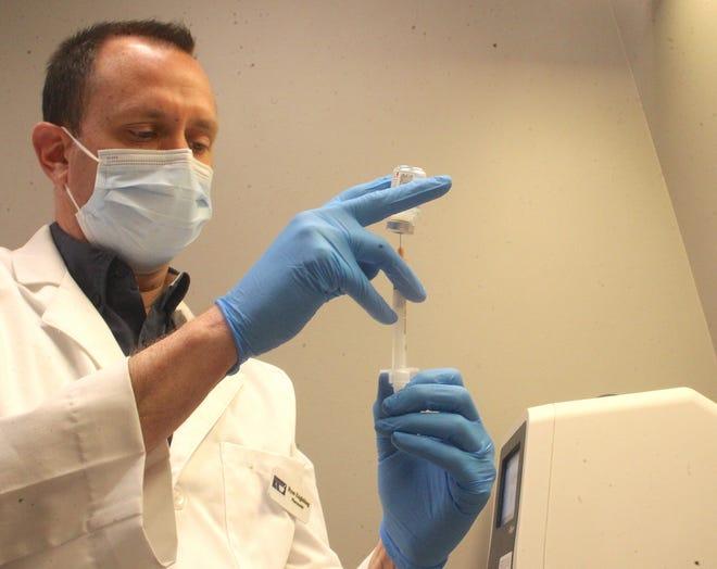 Pharmacist Ryan Engleking draws the Moderna COVID-19 vaccine into a syringe. (Garet Cobb / Times-Mail)