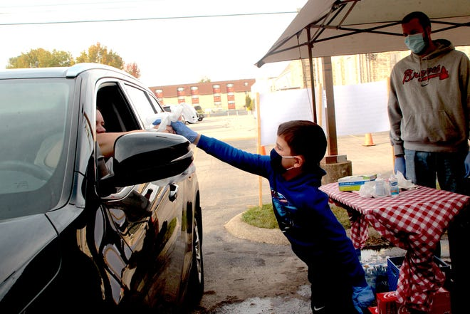 Devin Duffy hands a bag of drinks to a person using the drive through during Spaghetti at the Ready, a fundraiser for the Bedford Men's Warming Shelter in 2020. Devin's father Brian Duffy is in the background.