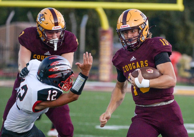 Bloomington North's Cody Mikulich (10) runs around a block from teammate Jack Recker (7) against Terre Haute South's Jacob Rutledge (12) for a touchdown during last year's game against Terre Haute South