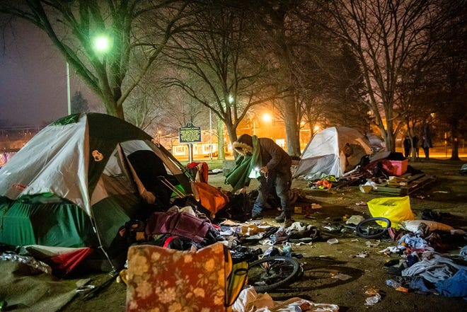 A man experiencing homelessness looks for an item Monday near a tent in Seminary Park. (Rich Janzaruk / Herald-Times)