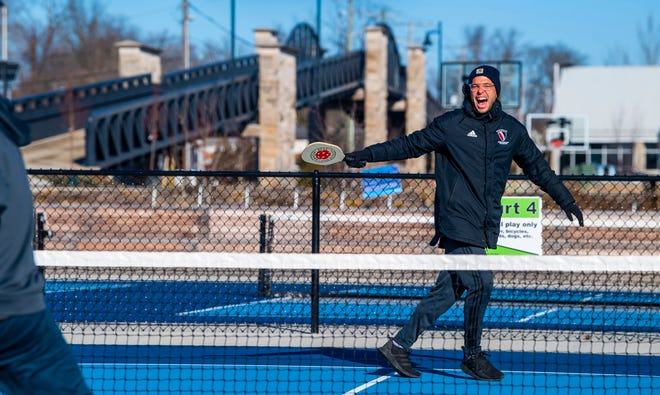 Mark Spiegel celebrates a point on the day after Christmas while playing pickleball at Switchyard Park. Despite temperatures in the 30s, sunny weather Saturday drew some people outdoors to enjoy some recreation. (Rich Janzaruk / Herald Times)