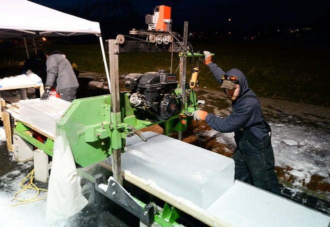 Dylan McDuffie cuts through a slab of ice Monday evening during the ice sculpting competition at Freezefest behind The Mill at the Trades District. (Bobby Goddin / Herald-Times)