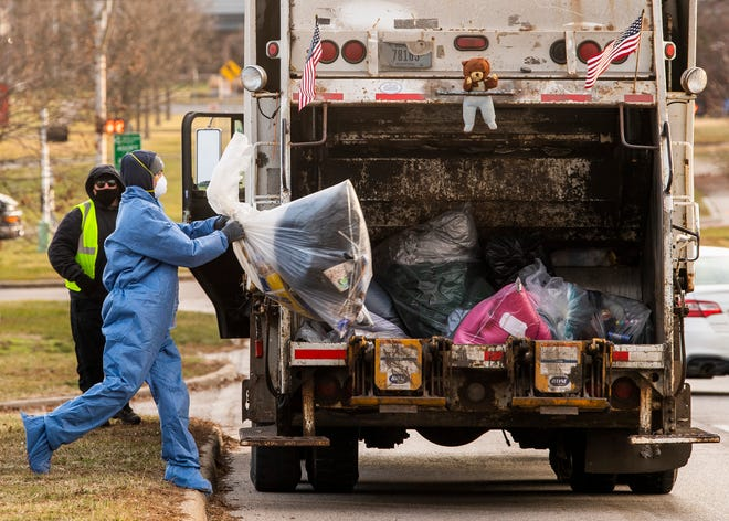 A city employee throws bagged items from Seminary Park into a garbage truck Jan. 15, 2021. (Rich Janzaruk / Herald-Times)