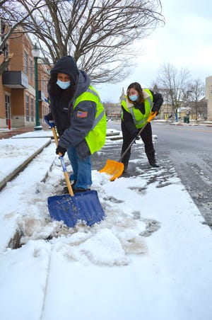 Jodi Wallace, left, and Sarah Ray shovel the handicapped parking spaces along Kirkwood Avenue on Monday morning after snow flurries left a coating of new snow on top of the icy remnants from previous days. The two are part of a crew working with the city's public works department in a partnership with Centerstone. (Carol Kugler / Herald-Times)
