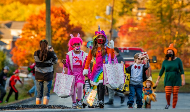 Lilah Gibson, center, Zion Hart, left in pink, Parker Stevens, right in bowtie, and Presley Stevens, right as scarecrow, head up to Monroe Fire Protection District's Station 22 Saturday to get some candy and treats from the firefighters. The station at 3953 S. Kennedy Drive was one of several in the county that took virus precautions to offer a safer trick-or-treating option this year. (Rich Janzaruk / Herald-Times)