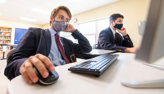 Tyler Neal, left, and Ryder Caswell, right, work with the coding club in May at Seven Oaks Classical School in Ellettsville. Officials at the school plan to make face mask use optional this school yea, in defiance of a county health order.