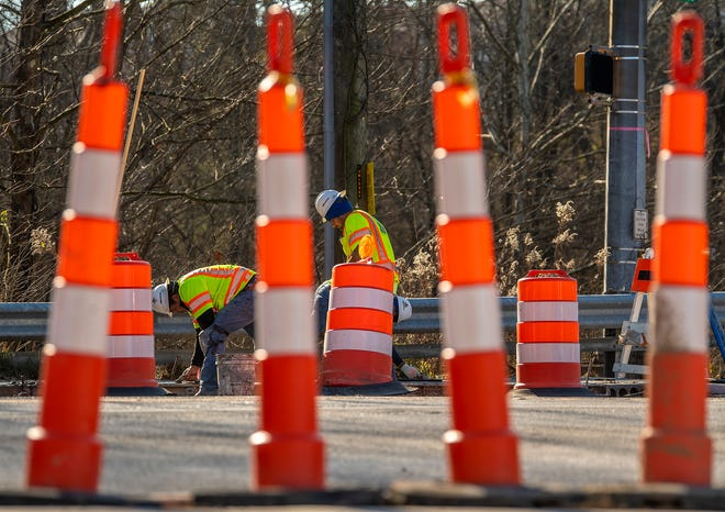 Construction crews smooth out recently poured concrete Wednesday on a sidewalk and drainage improvement project at the intersection of College Mall Road and Sare Road. (Rich Janzaruk / Herald-Times)