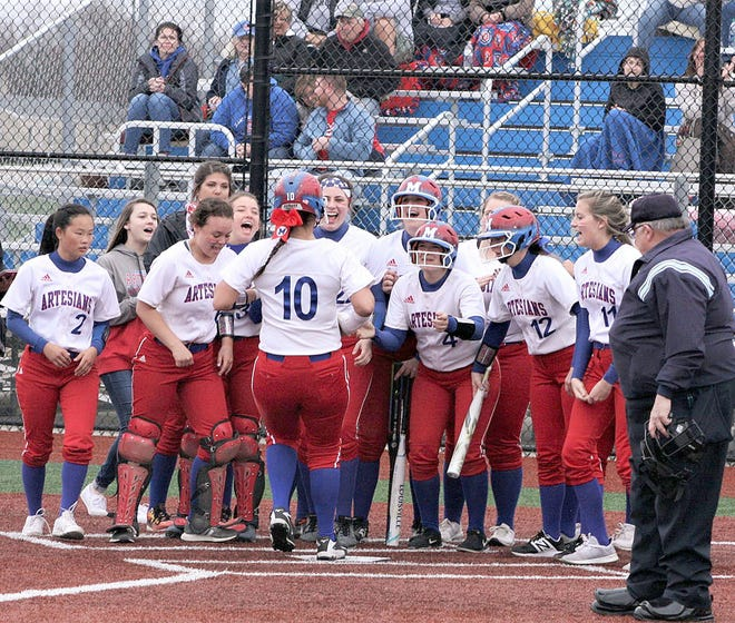 Martinsville players greet Paige Dorsett after she hit a home run in last season's Mid-State Conference game at Mooresville (Steve Page / Correspondent)