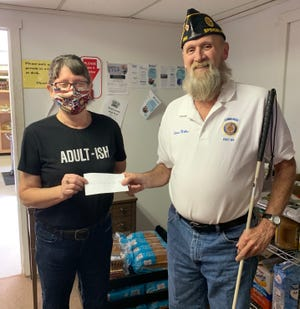 Mark of Discipleship Food Pantry volunteer Paula Bault receives a $1000 check from American Legion Commander LD Miller. (Submitted / Spencer Evening World)