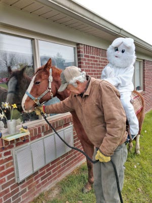 """Recently the local 4-H Fishing Team Club visited Owen Valley Health Campus, taking animals to the windows of the facility for residents to see. The group also created positive messages in chalk for the workers. Team members stayed six feet apart and watched as the residents smiled and laughed. The Easter Bunny even sat atop a horse, waving """"Hello"""" to the residents. (Submitted / Spencer Evening World)"""