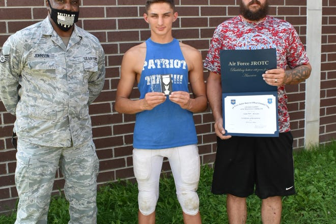 Seth Brewster, center, received the Air Force ROTC Silver Valor Award for his a heroic rescue of an Ellettsville woman from her home, with the assistance of his father, Mark Brewster, right, during a house fire in November 2019. The pair is pictured next to Staff Sergeant Alfred Johnson, left, who nominated him for the award, which he received in August 2020. (Casey Shively / Spencer Evening World)