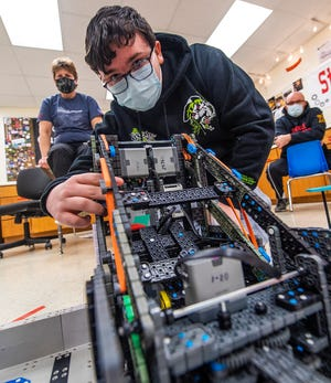 Noah Baynum makes an adjustment to the robot as head coach Whitney Goodwin, left, and assistant coach Nate Hancock, right, watch while practicing Jan. 21 at the old Stinesville Elementary building.