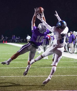 Bloomington South's Maddix Blackwell (18) catches a pass over Columbus North's Jaxson Scruggs (3) during the fourth quarter of Friday night's game.