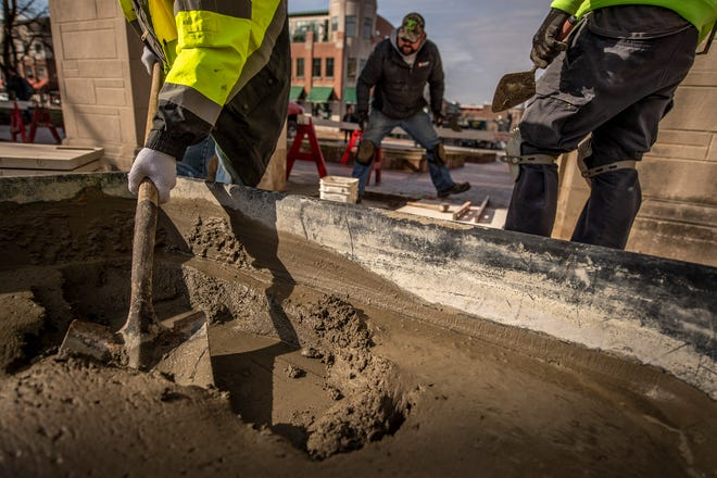 Danny McNew, with Indiana University, scoops concrete Tuesday as he, Chris Clark, middle, and Kenny Wagner work on placing new stone walkway pieces around the Sample Gates on Indiana Avenue. (Rich Janzaruk / Herald-Times)