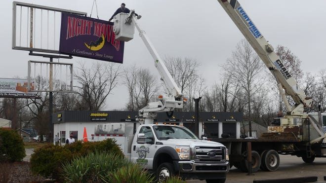 A crew with Everywhere Signs and Crane Service in Bloomington removes the Night Moves sign Friday afternoon. The local strip club no longer operates out of the purple building at 1730 S. Walnut St. (Ernest Rollins / Herald-Times)