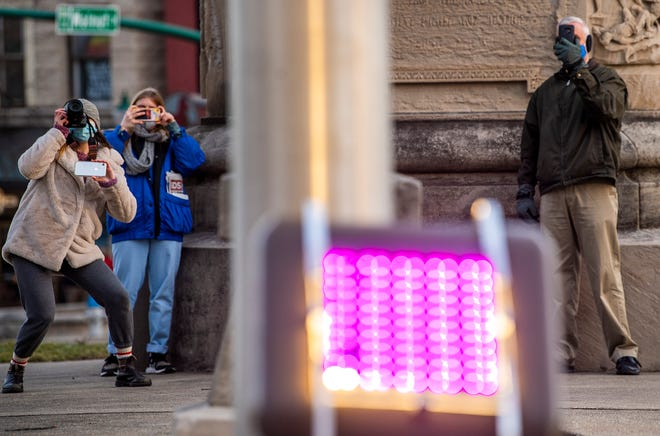 Indiana Daily Student photographer Anna Brown, left, takes images and records video Tuesday of the Monroe County Courthouse as its bell rings once for each county resident lost to the coronavirus. Indiana Daily Student reporter Madi Smalstig, middle, also recorded the event while Andrew Lambert, right, live-streamed the event for the Monroe County commissioners. (Rich Janzaruk / Herald-Times)