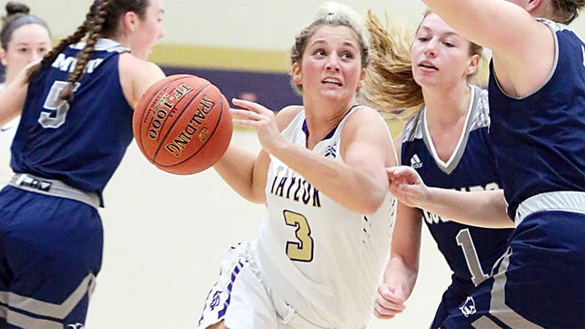 Taylor University junior Merideth Deckard handles the ball during the game with Oakland City. Deckard led the Trojans with 24 points and tied a team record with eight three-pointers. (Taylor University photo)