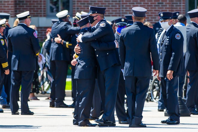Attendees embrace one another Wednesday after the funeral for South Bend Firefighter Jeremy Bush at Saint Pius X Catholic Church in Granger.