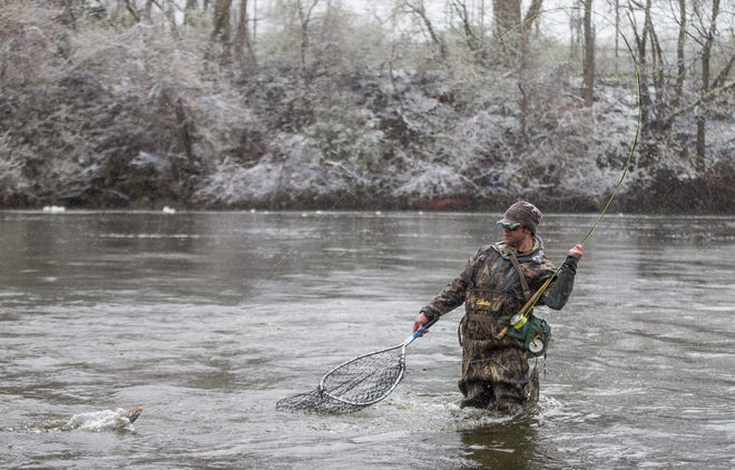 Rob Siri, of Galien, catches a steelhead trout in the St. Joseph River as a late-season snowfall blankets the area on Wednesday, April 15, 2020, at Leeper Park in South Bend. Heavier snow is expected early Friday morning in Michiana.