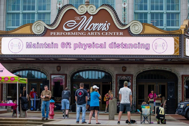 A sign encouraging physical distancing flashes on the marquee while Jerica Paliga performs during the Fridays by the Fountain near the Morris Performing Arts Center in downtown South Bend.
