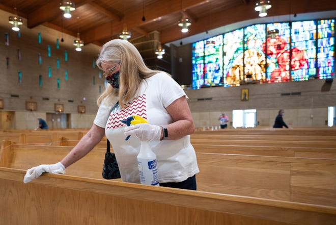 Susan Clark was one of several volunteers who stayed to disinfect pews following Saturday services at St. Matthew Cathedral in South Bend.