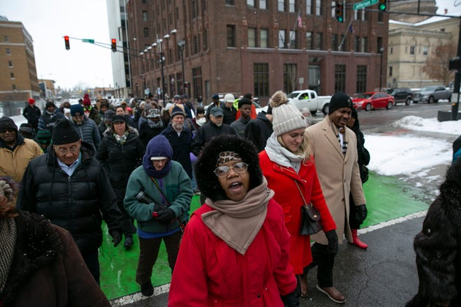 Community leaders and others participate in the annual MLK march from the County-City building to the Century Center on Monday.