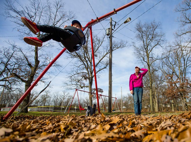 Lindsay Koriath pushes her 2 and a half-year-old son Ian McNeil on the swings Thursday, Nov. 19, 2020 at Veterans Memorial Park in South Bend.