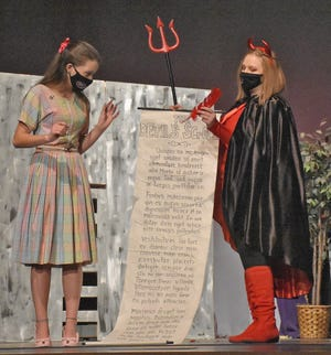 The girl (Lexi Pinkard) gets ready to sign a deal with the devil (Mady Dill) during the 'Girl Strikes a Bargain' piece in Act I. (Amanda York / Spencer Evening World)