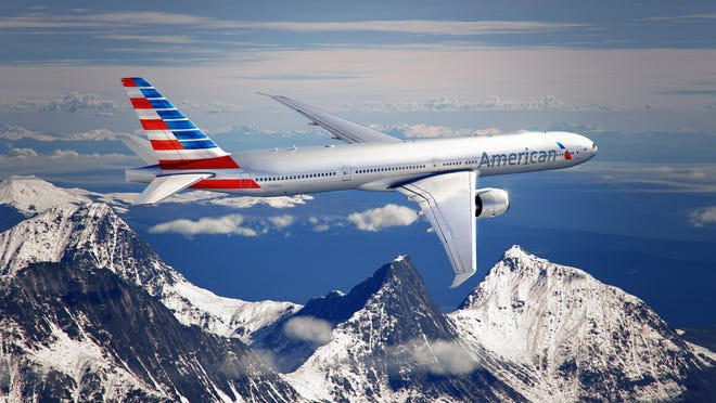 An American Airlines jet flies over a mountain range.