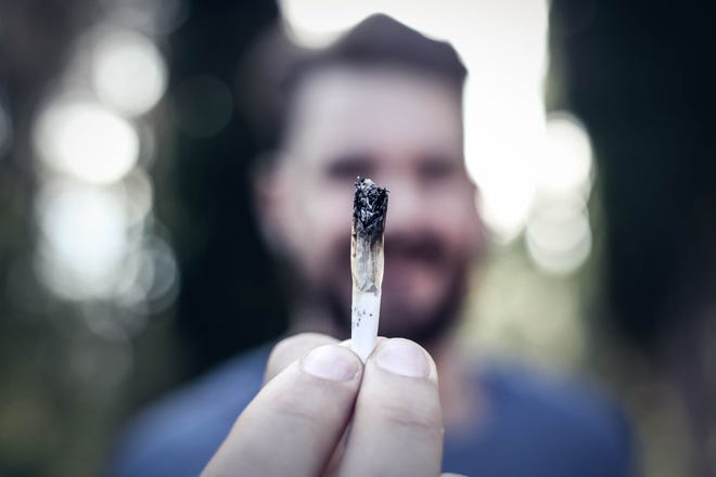 A man holding up a lit cannabis joint by his fingertips.