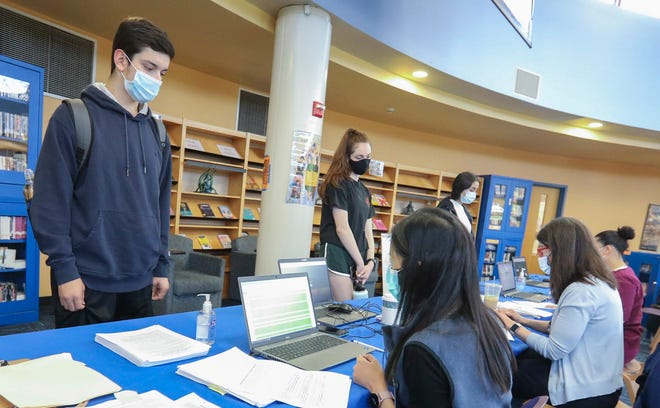 White Plains High School student Michael Grande, 17, checks in to receive his first COVID-19 vaccination at a clinic set up in the library of White Plains High School in New York on May 4.