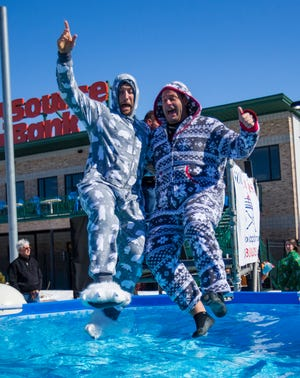 RIGHT: Jason Kwiecinski, left, and Jeff McKinley leap into the ice cold pool of water.