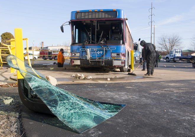Crews work to clean up after a Transpo bus crashed into a truck dock connected to the United Coatings Technologies building on Wednesday in South Bend.