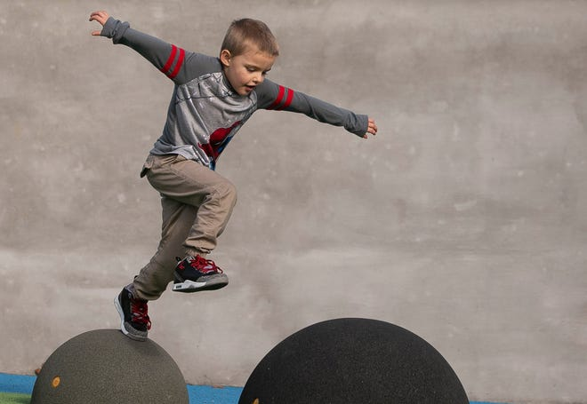 Aaron Boothe, 6, bounces around from obstacle to obstacle as he plays at Howard Park during a warm February day.