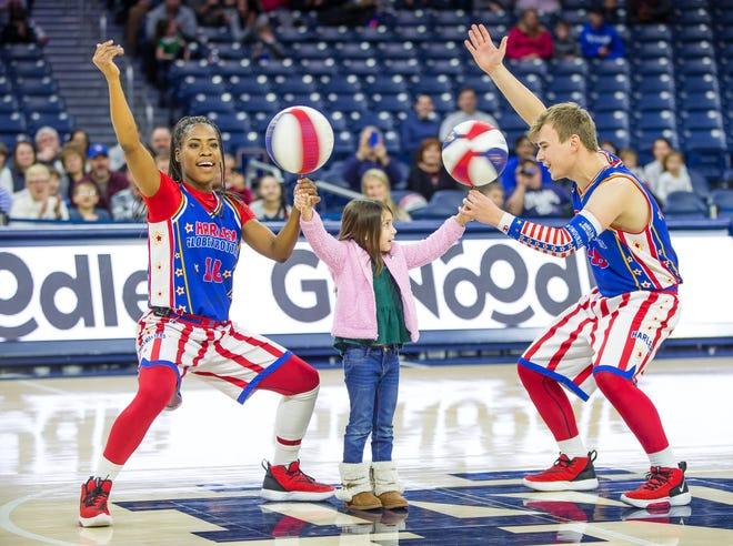 TNT Lister and Dazzle Kidon help 5-year-old Mackenna Delgado spin basketballs.
