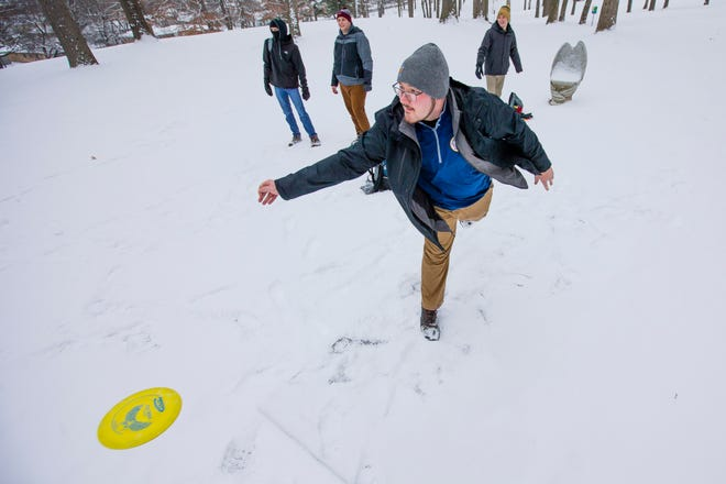 Western Michigan University student Matthew Pruitt takes a shot as William Buettner, back from left, Michael Coldagelli and watch while playing disc golf Monday, Jan. 18, 2021 at Rum Village in South Bend. The group came down to play the course and get food at Portillo's.