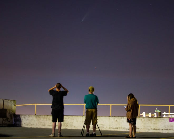 Joe Black, from left, Jon Gilchrist and Melaney Miller look at Comet NEOWISE visible from atop the Colfax parking garage Thursday, july 16, 2020 in downtown South Bend.