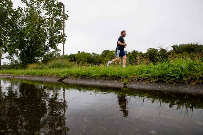 A runner goes past a puddle Tuesday on Northside Boulevard in South Bend.