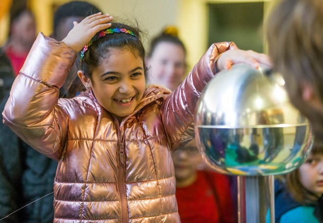 Sara Kazi, 8, smiles as her hair stands up while touching an energized metal sphere at the QuarkNet Center exhibit Saturday during the 28th annual Science Alive in the Jordan Hall of Science at the University of Notre Dame.