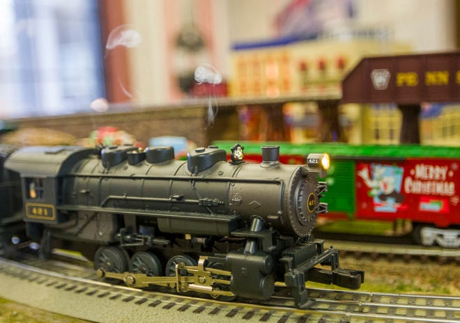 A model train runs on a track and puffs off makeshift smoke inside New York Central Toys and Trains in Mishawaka.