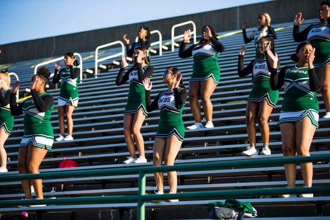 Washington High School cheerleaders socially distance in the stands during the Friday night game at School Field in South Bend.