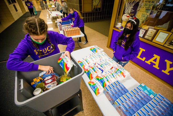 Clay junior Alexa Hunt, left, gets help packing a basket from classmate Belen Pacheco-Salazar during the Clay student council Season of Service food basket assembly Monday at the South Bend high school.