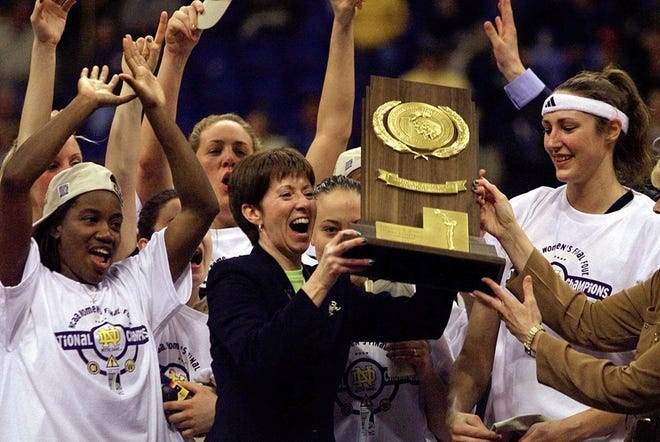 Notre Dame coach Muffet McGraw, center, holds up the National Championship trophy after Notre Dame defeated Purdue, 68-66, to win the 2001 national championship. At left is Imani Dunbar and Ruth Riley is at right.