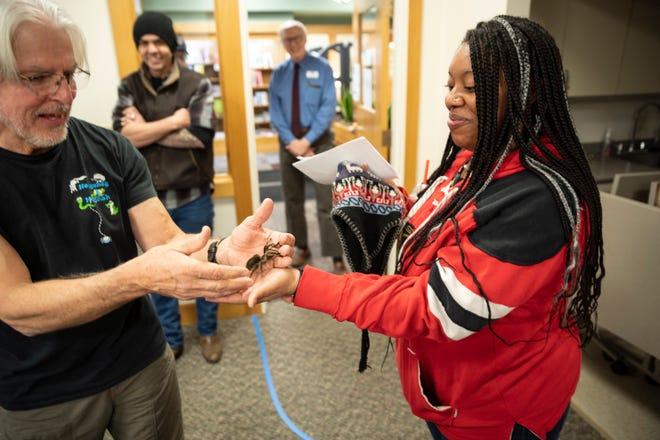 Paul Venckus with Hannah's Hedgehog places a tarantula on the hand of Ashley Lauderdale.