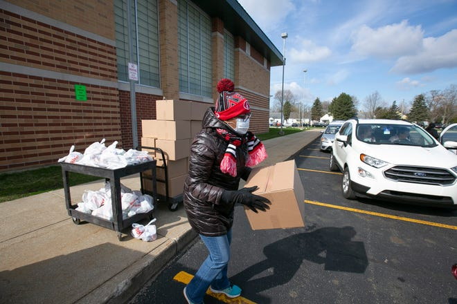 """Karla Lee, principal at Harrison Elementary School, loads a box and other supplies into a car. School staff distributed more than 500 """"family care boxes"""" on Tuesday."""