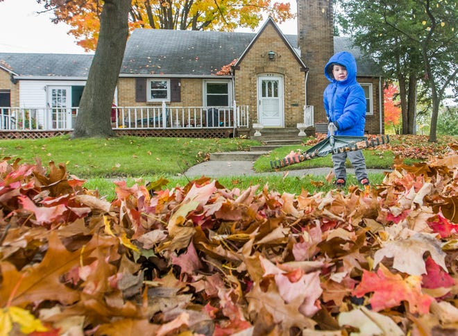 Three-year-old Davis Kirk rakes leaves outside his home on Friday, Oct. 30, 2020, in South Bend.