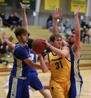 Presentation College's Jackson Becker, center, looks to pass the ball between Trinity Bible College's Jackson Holt, left and Logan Klitzke, right, during Tuesday night's game at the Strode Activity Center. American News photo by John Davis taken 11/24/2020