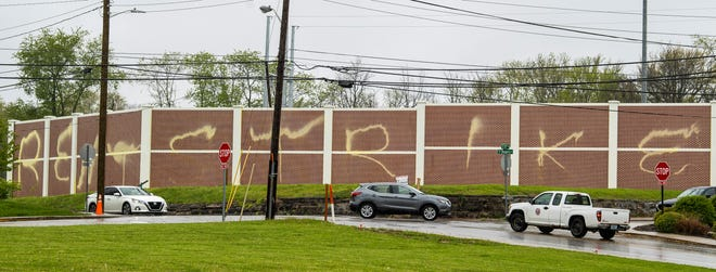 """Traffic drives Thursday through the 11th Street and Rogers Street intersection, where graffiti saying """"Rent Strike"""" has been painted on a brick wall. (Rich Janzaruk / Herald-Times)"""